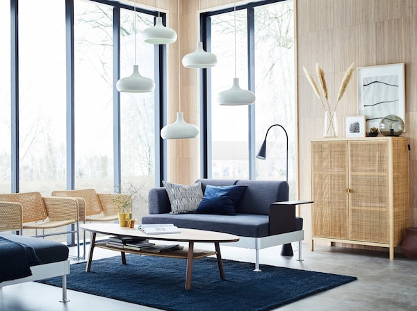 A light-filled beige, blue and grey living room with large windows and a DELAKTIG 2-seat sofa in anthracite with side table.