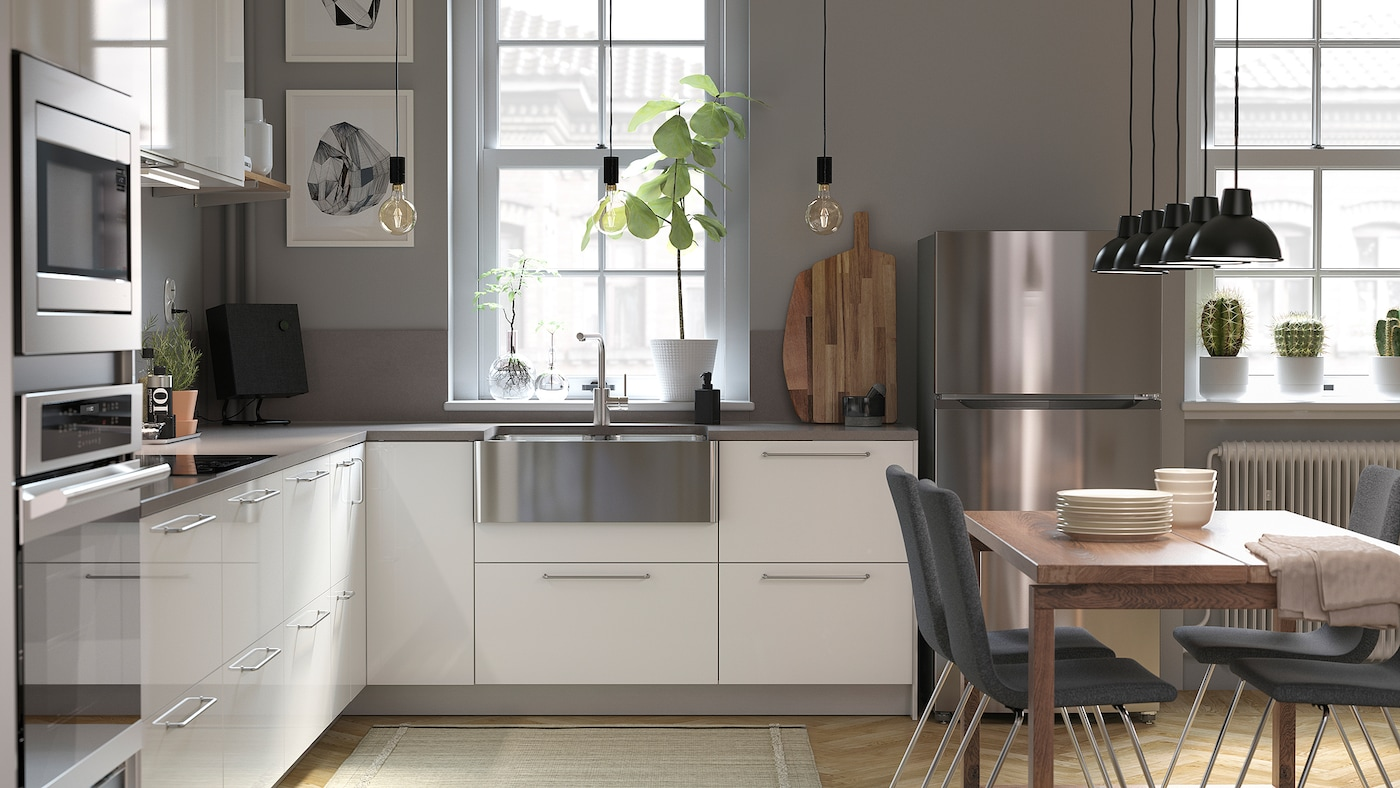 A light-filled kitchen with white shiny drawer fronts, gray walls, a wooden table, and a stainless steel sink.