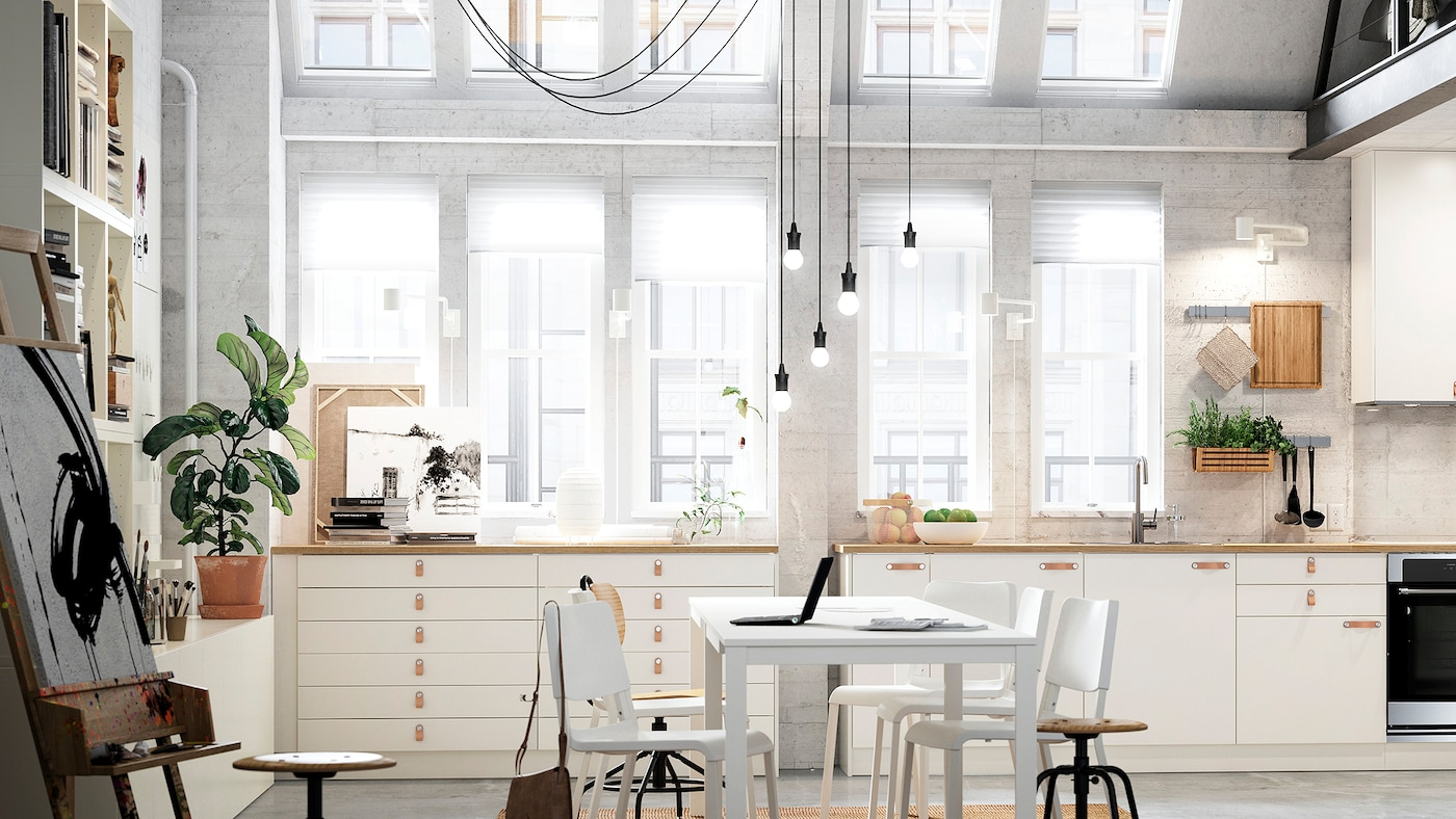 A light-filled open kitchen in a loft with two rows of cabinets with white VEDDINGE doors and a white table and chairs.