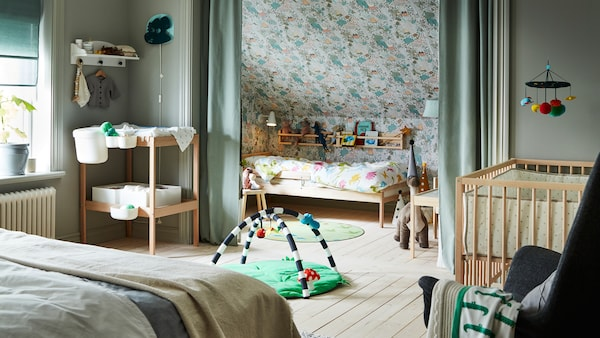 A light green bedroom containing a double bed and SNIGLAR cot, bed and changing table, with a KLAPPA baby gym on the floor.