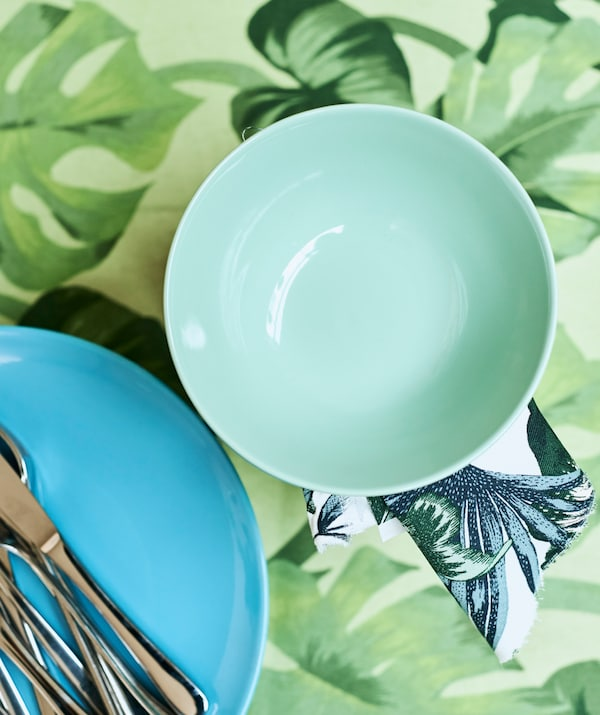 A light green bowl next to a turquoise plate with cutlery on top, on a table covered with green leaf-print fabric.