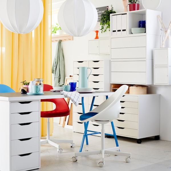 A light grey/white/blue table with drawer unit, two swivel chairs in white/blue/red, white drawer units and yellow curtains.