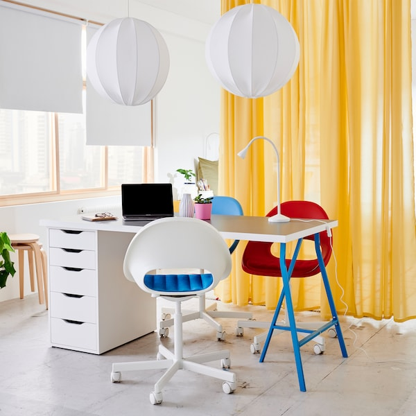A light grey/white table with blue legs and drawer unit, white round pendant lamps, three swivel chairs and yellow curtains.