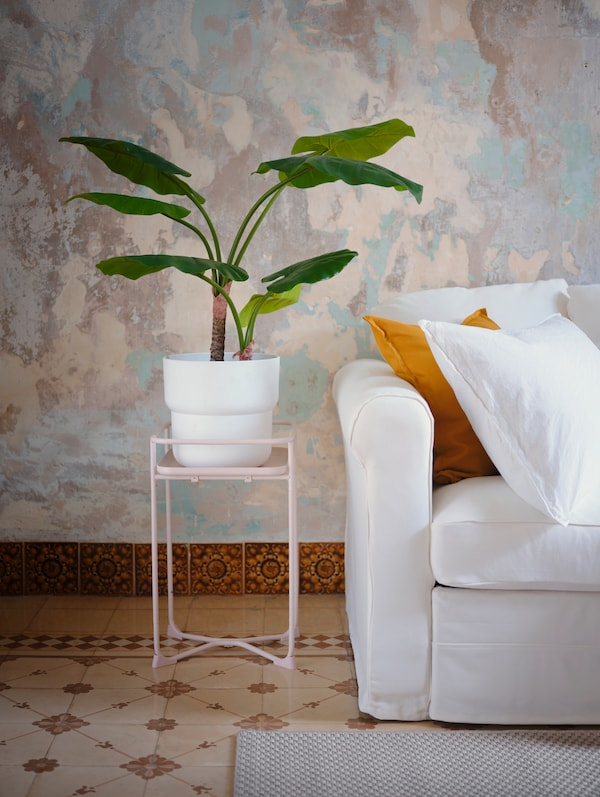 A light pink plant stand with a pot plant placed on top of it, standing next to a white sofa with throw pillows.