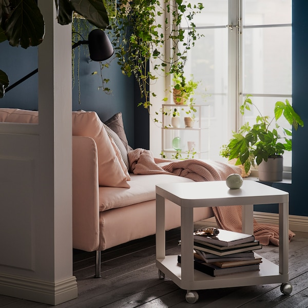 A light pink SÖDERHAMN sofa facing two windows with a TINGBY side table beside it, surrounded by lots of lush green plants.