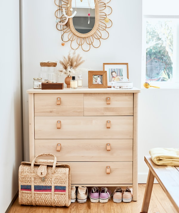 A light wood chest of drawers, with wicker-framed mirror on the white wall above, and a wicker bag and trainers underneath.
