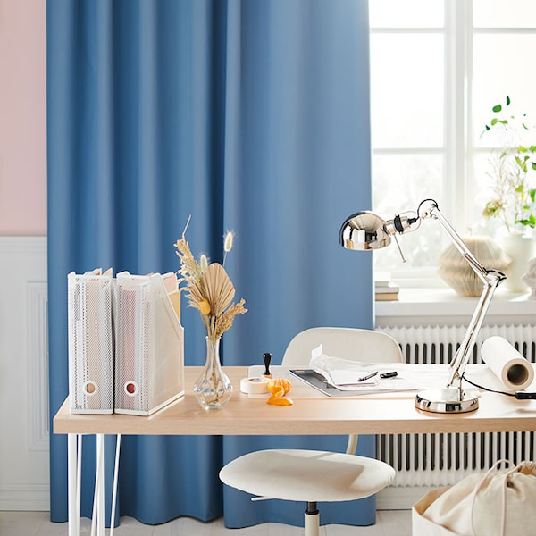 A light wood desk with white accessories, in front of a window with sky blue curtains.
