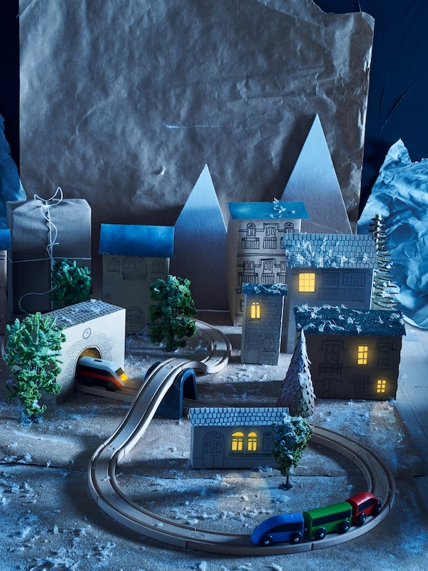 A LILLABO train set placed within a cardboard cut out town at night, with yellow lights at the house windows.