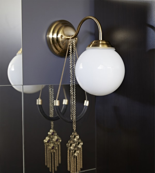 A LILLHOLMEN wall lamp has a brass-colour base, thin rounded neck and white glass globe.