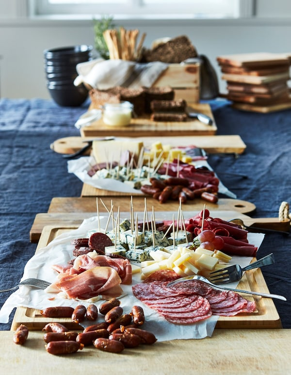 A line of chopping boards covered in a variety of meats and cheeses on a dining table.
