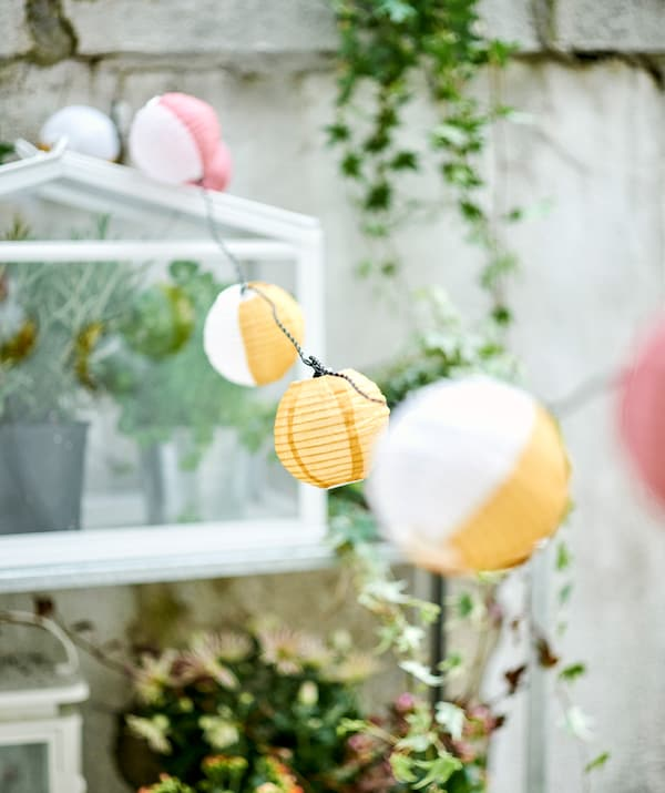 A line of small round paper lanterns, some yellow and white, some pink and white, strung across a balcony with trailing ivy.