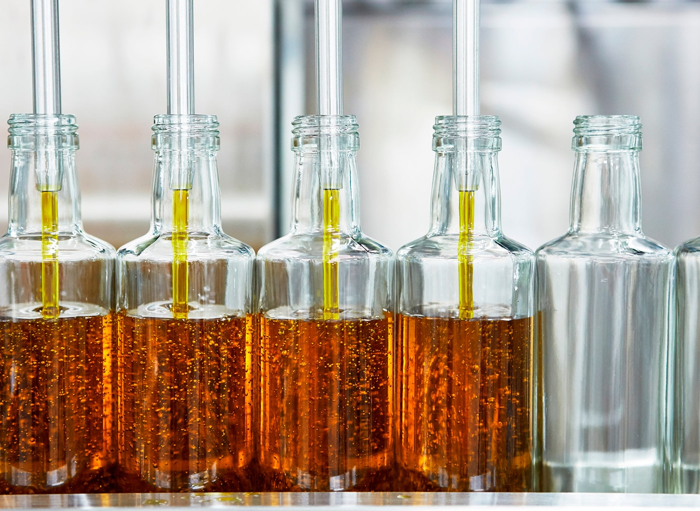 A lineup of glass bottle being filled at a factory with canola oil.