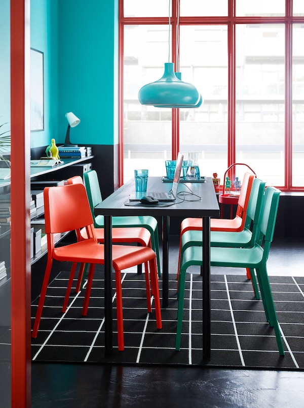 A LINNMON/ADILS table with turquoise and red chairs on a black and white check rug. A turquoise pendant lamp hangs above.