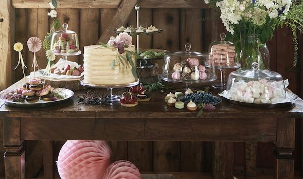 À l'intérieur d'une grange se trouvent des décorations et d'autres produits de la collection INBJUDEN, notamment des assiettes, une nappe pliée, des housses de coussin et des vases.