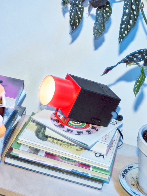 A lit IKEA FREKVENS spotlight accessory kit in black and red standing on a pile of books.