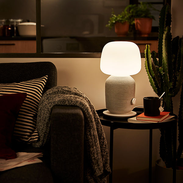 A lit SYMFONISK lamp on top of a small side table in a dark living room.