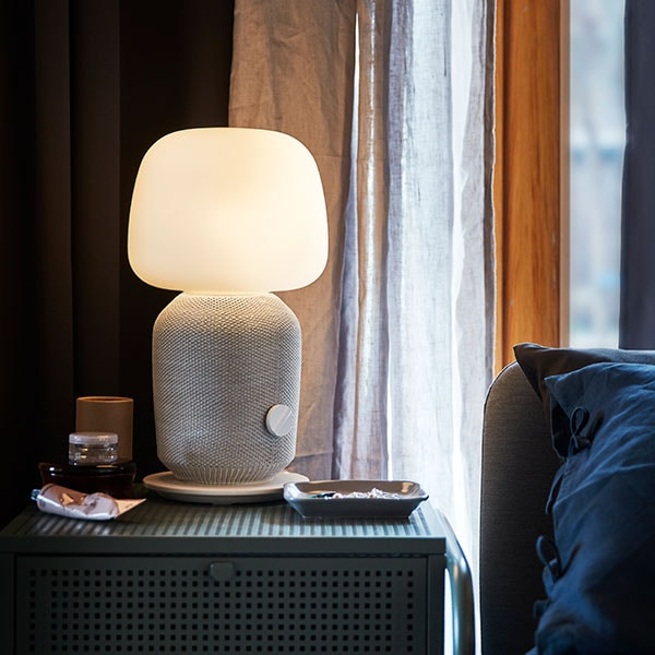A lit SYMFONISK table lamp on a nightstand next to a bed.