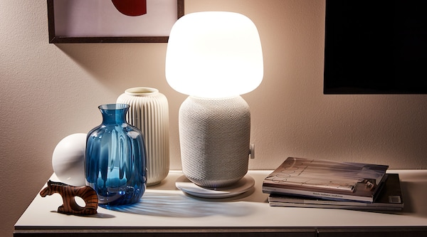 A lit SYMFONISK table lamp speaker on top of a table surrounded by home decor products.