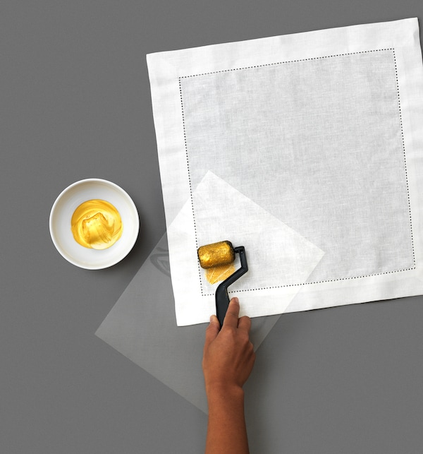 A little DIY goes a long way to make custom, decorative napkins using white GULLMAJ cloth napkins from IKEA. The third step is to place the cut-out plastic stencil on the napkin. Then use a roller to apply fabric paint onto the napkin.