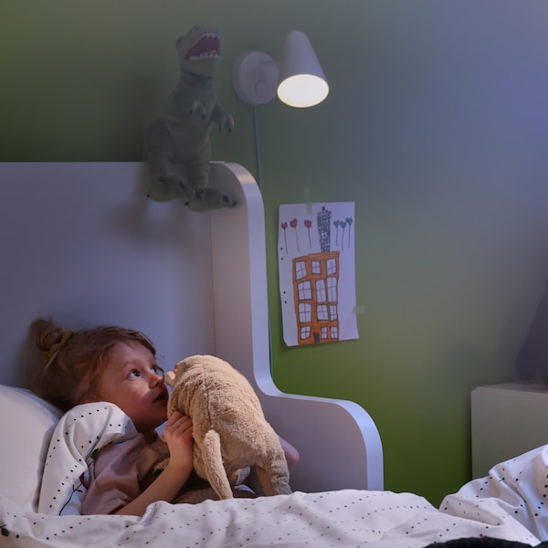 A little girl lies in bed and whispers to her favourite soft toy. A FUBBLA wall lamp attached to the wall brightens her room.