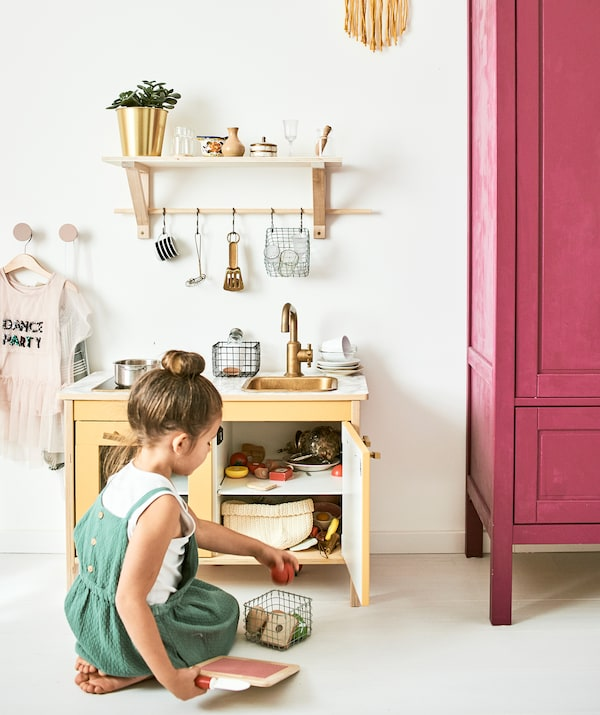 A little girl plays with a mini kitchen with accessories including toy pans, food and cooking utensils hanging from a shelf.