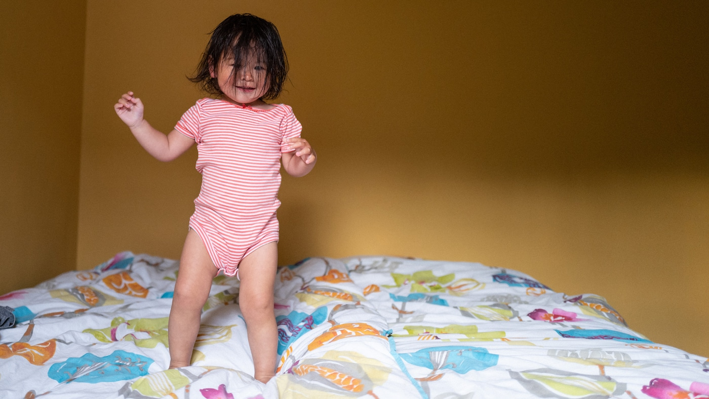 A little girl with dark hair all over her face is jumping on a bed. She is having fun.
