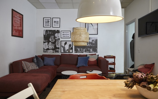 A living area with sofa, lighting and picture frames on the walls.