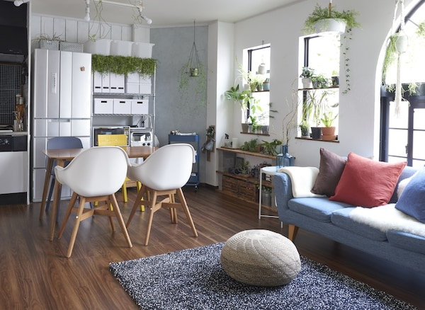 A living area with sofa, rug, dining table and chairs and storage boxes against the wall.
