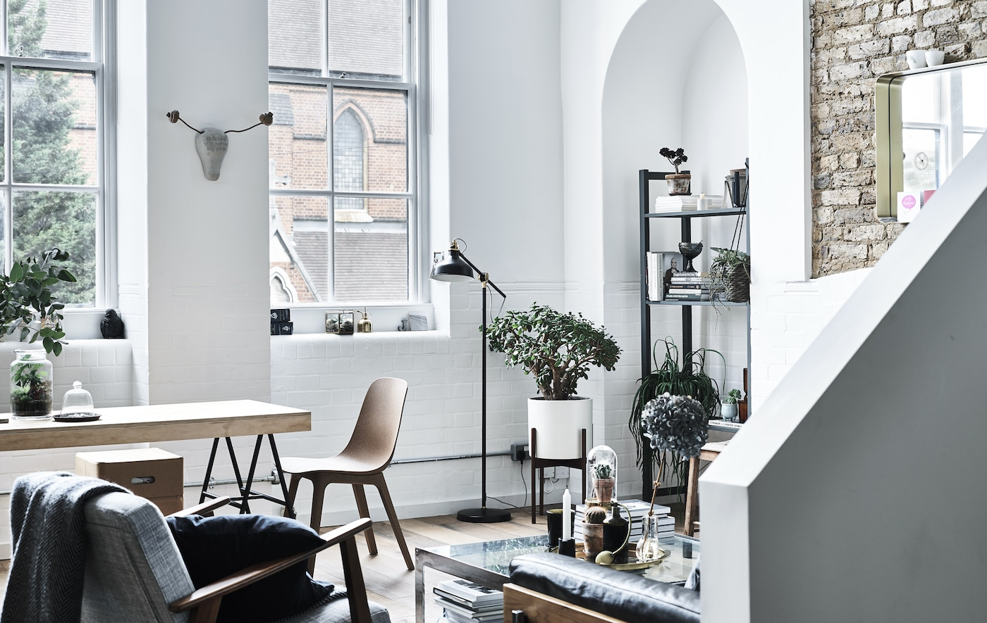 A living room and dining area with white walls in a converted apartment, in an old school.