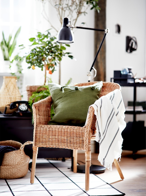A living room area in black, white and green with large plants, an AGEN rattan chair and accents in natural materials.