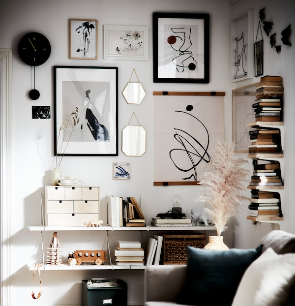A living room area with secondhand books, accents in natural materials and an art wall in white, black and oatmeal.