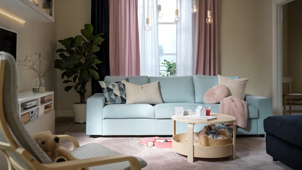 A living room in a pastel colour scheme with a light-blue VIMLE sofa, light-pink KALKFLY curtains and a BORGEBY coffee table.
