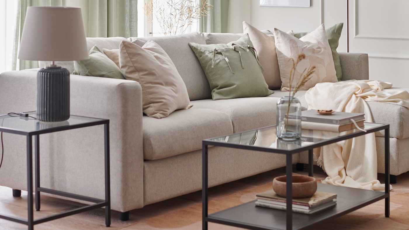 A living room is furnished for spring with a FINNALA sofa, RÖDASK cushion covers and SNÖBYAR lamp on a VITTSJÖ table.