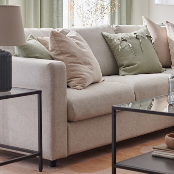 A living room is furnished for spring with a VIMLE sofa, RÖDASK cushion covers and SNÖBYAR lamp on a VITTSJÖ table.