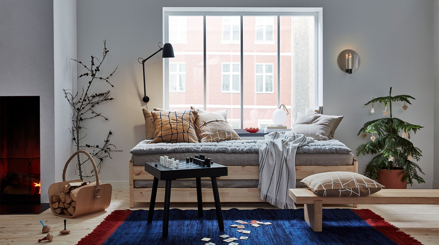 A living room is shown with VÄRMER items: cushions, wooden bench, boardgame, rug, basket, spinning tops and wall sconce.