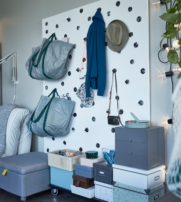 A living room storage wall created with hooks for hanging clothes and bags and storage boxes stacked on the floor.