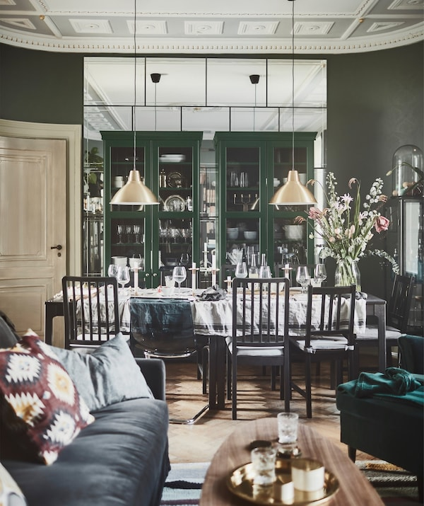 A living room that leads directly to a dining area, with two IKEA LIATORP bookcases with glass doors.
