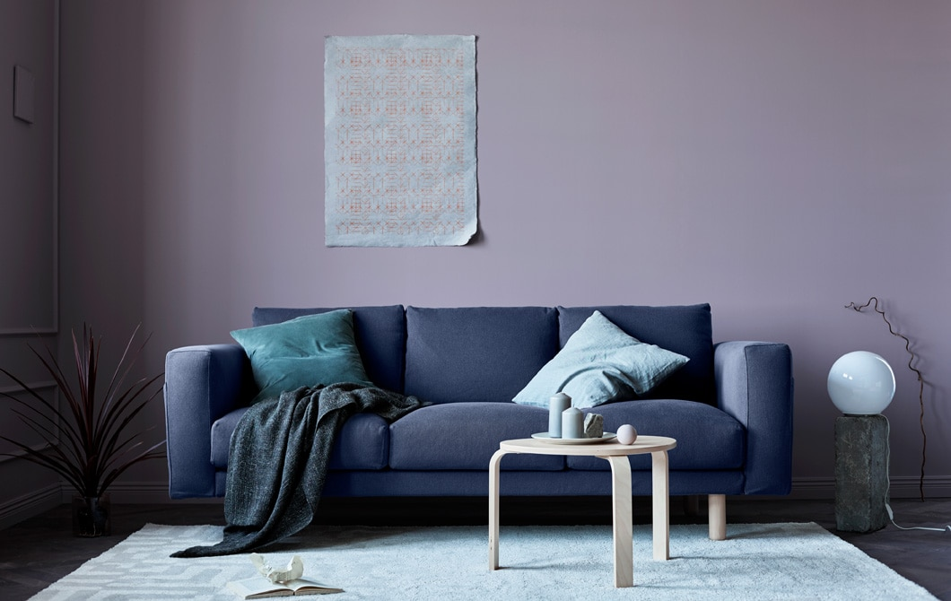 A living room updated for fall with a grey sofa, pink walls, blankets and natural elements