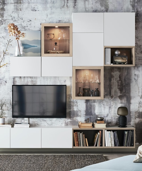 A living room wall with white and stained oak BESTA storage system.