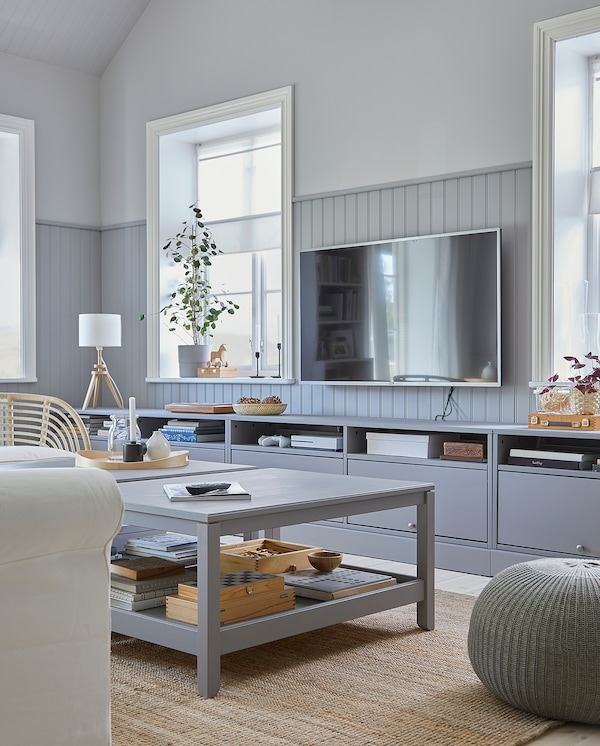 A living room where a gray HAVSTA TV bench with plinth and two grey HAVSTA coffee tables create a coordinated style together.