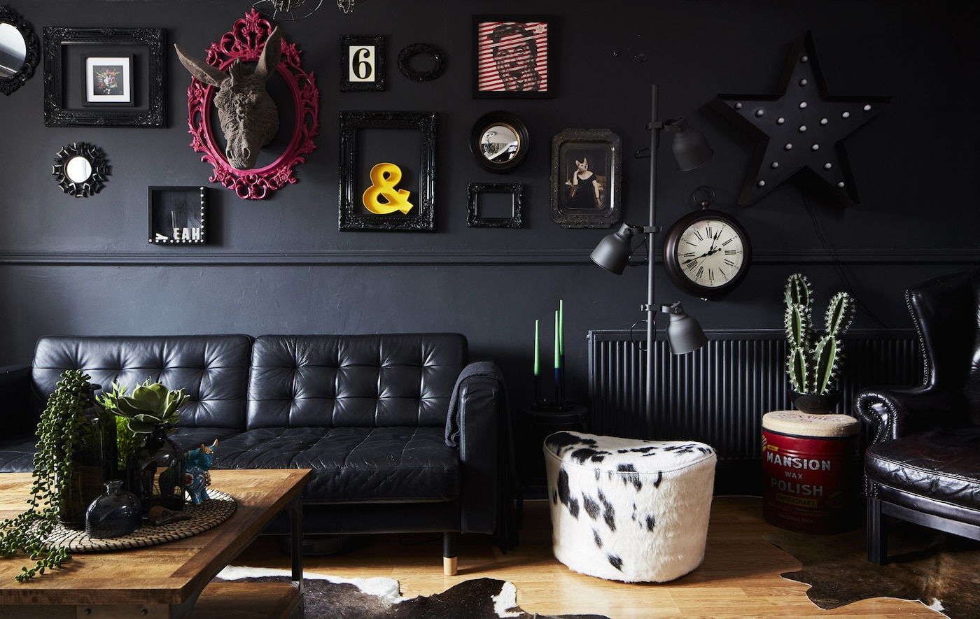 A living room with a black leather sofa and a cowhide footstool in black and white, against a black wall with picture frames.