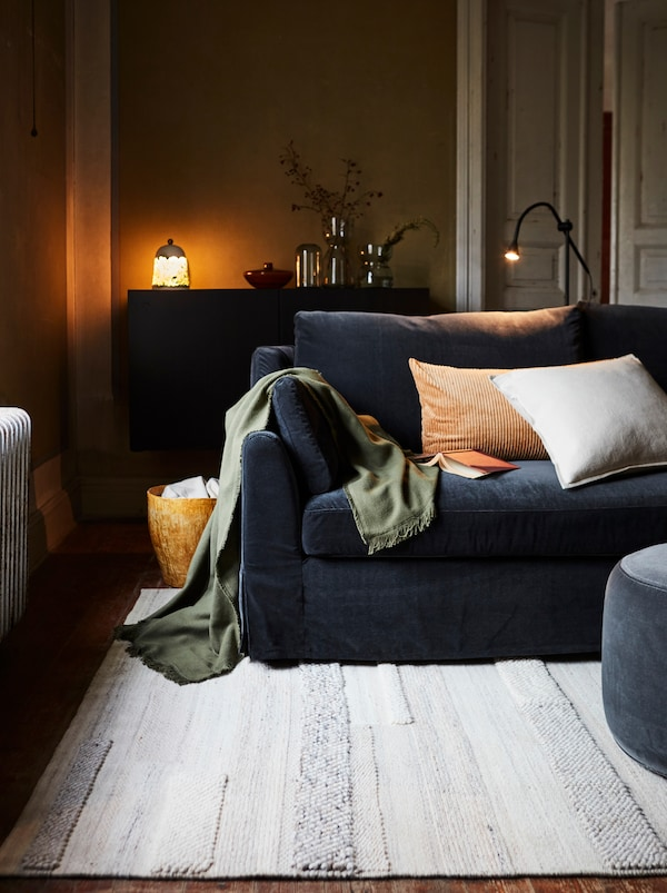 A living room with a dark sofa, cream-colored rug, cushions and blanket, floor lamp, and sideboard with decorative objects.