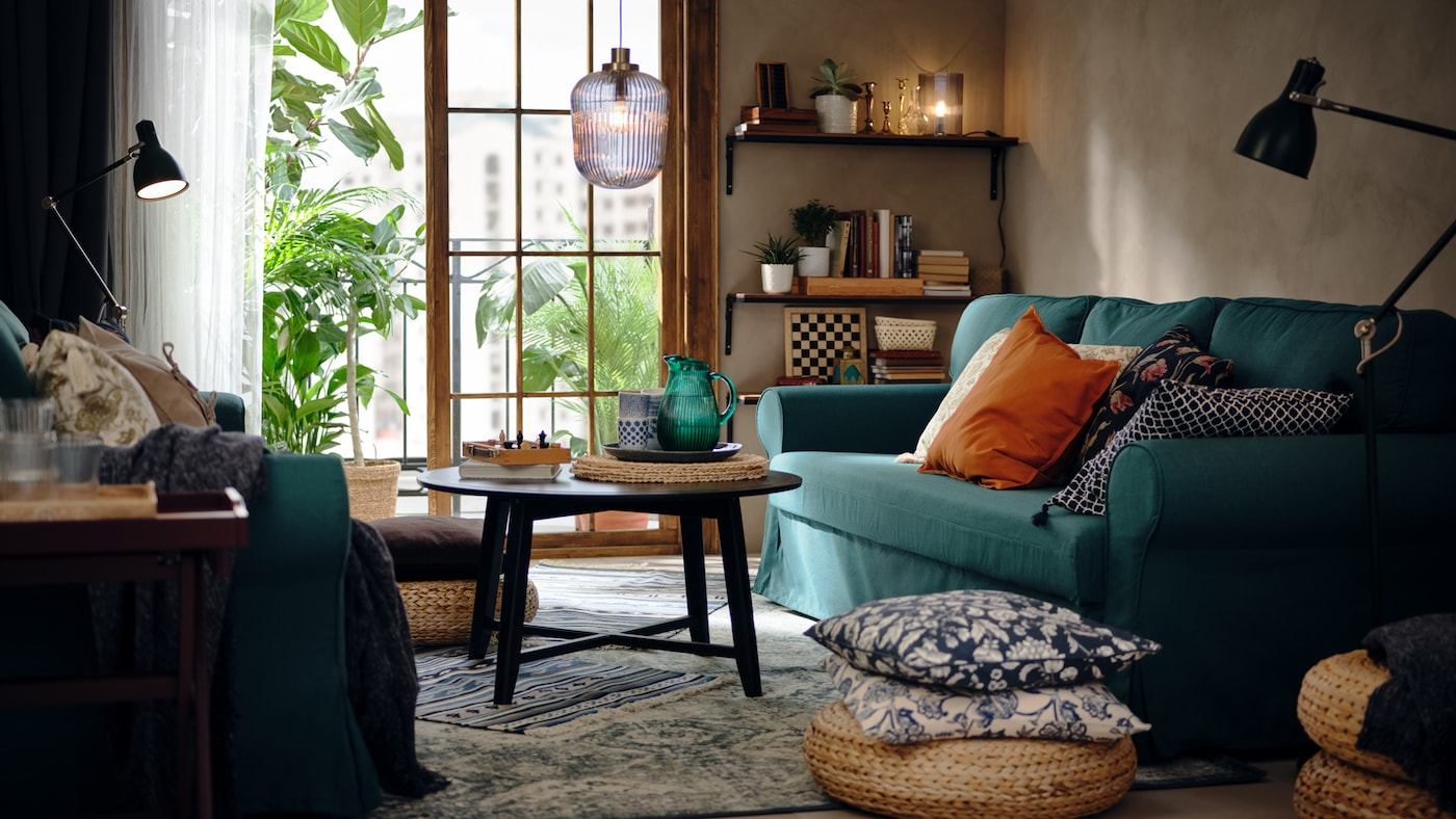 A living room with a dark-turquoise VRETSTORP three-seat sofa-bed, an ALSEDA banana-fibre stool and a KRAGSTA coffee table.