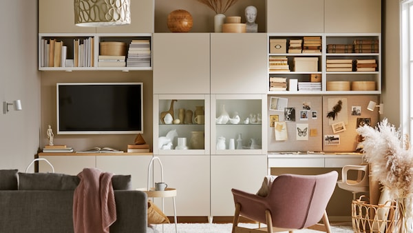 A living room with a grey-beige BESTÅ storage system giving the wall open and hidden storage, a sofa, a TV and a workstation.