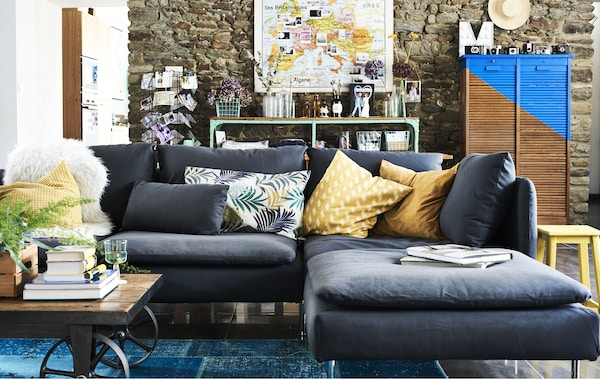 A living room with a grey sofa section with chaise lounge and colourful cushioned textiles.