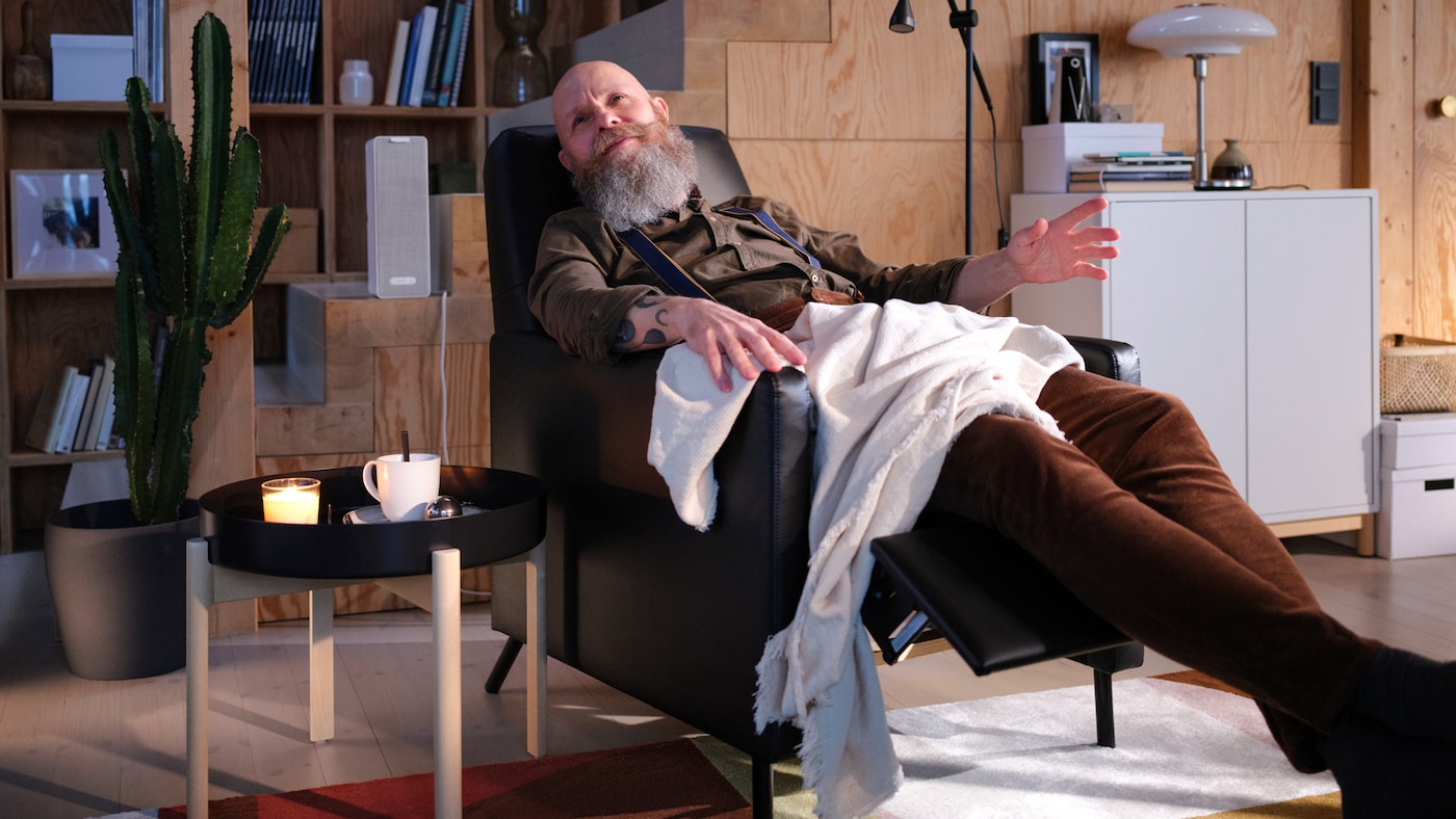 A living room with a man sitting in a black GISTAD recliner listening to music beside a coffee table with a cup of tea.