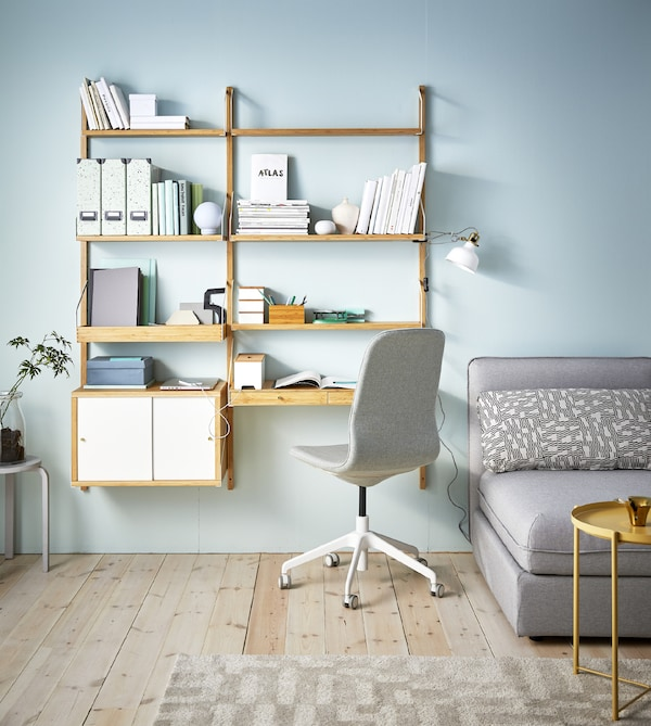 A living room with a sofa and a wall of modern bamboo shelves including one shelf that's a desk.