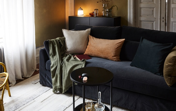 A living room with a sofa, cushions, throw, rug, a small table, a sideboard with a lamp, vases, and a rattan armchair.