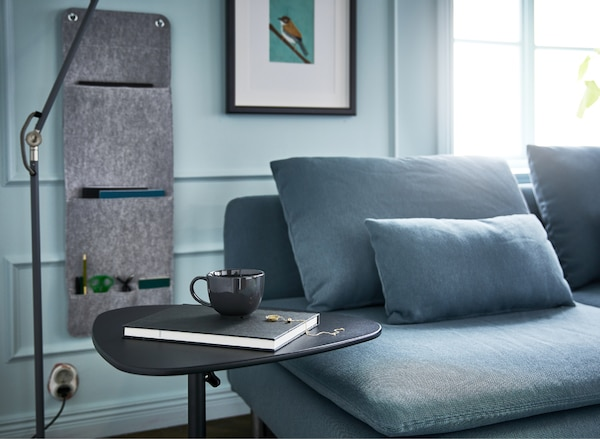 A living room with a sofa, floor lamp, hanging wall organiser and adjustable laptop stand for an efficient couch desk.