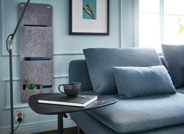 A living room with a sofa, floor lamp, hanging wall organiser and adjustable laptop stand for an efficient sofa desk.